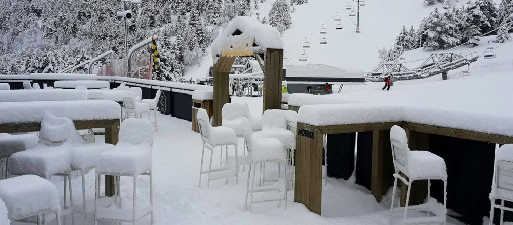 Snow piled up on tables and chairs by the ski slopes