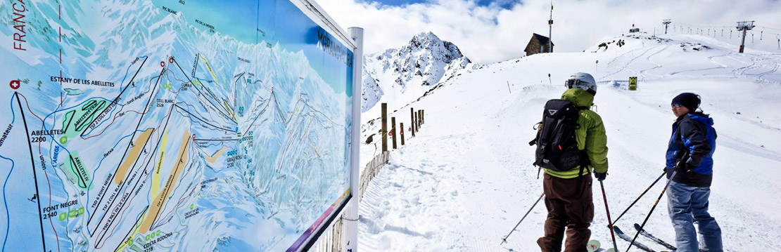 Skiers next to Grandvalira piste map